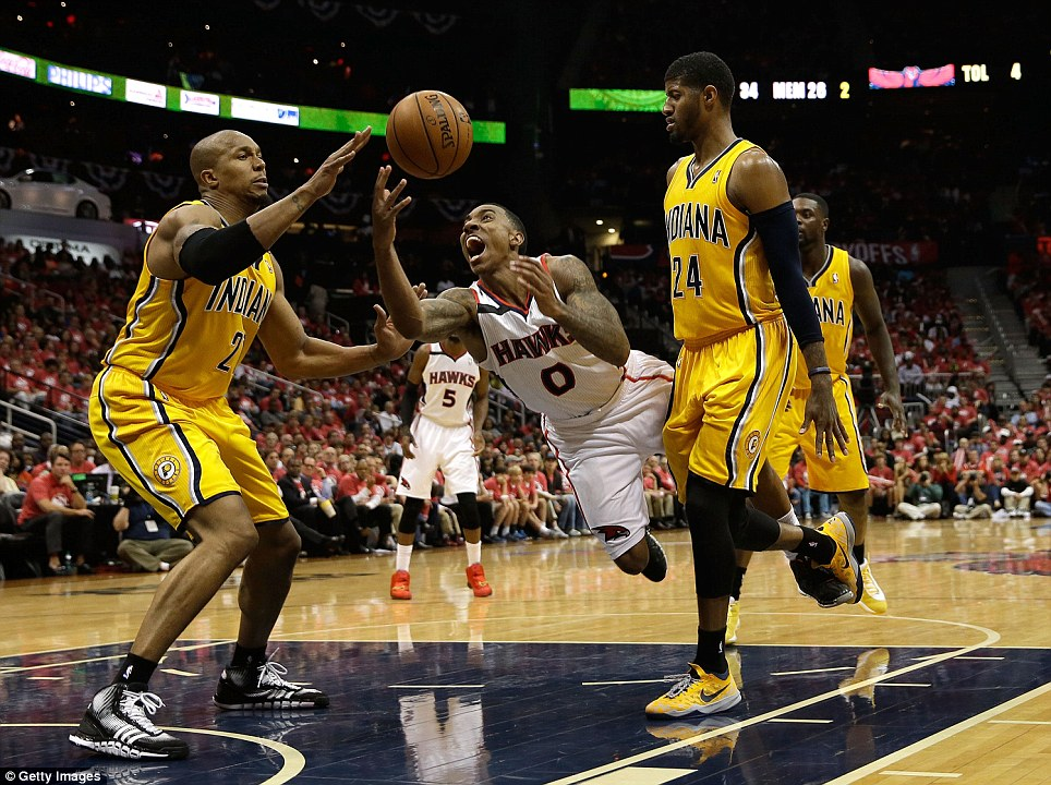 Attacking intent: Jeff Teague (centre) of the Atlanta Hawks is fouled by forward Paul Geroge (right) of the Indiana Pacers during Game 6 of the Eastern Conference quarter-finals