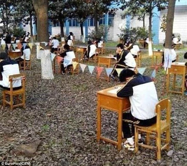 Hot desking: Teachers at the school, in Jinzhou city in Hubei province, were worried their pupils might overheat during their end-of-term tests so they moved all tables and chairs outside