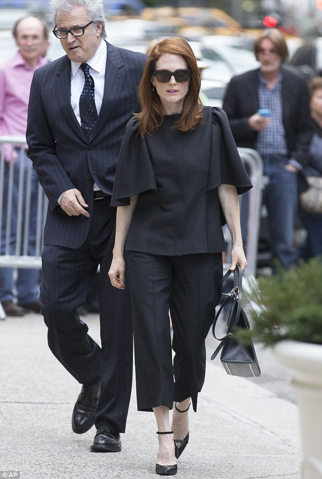 Solemn occasion: A black-clad Julianne Moore arrives at the church on Friday in Manhattan