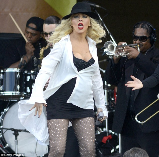 Baby on board: Christina Aguilera showed off her growing bump and an eyeful of cleavage in a little black dress on stage at the New Orleans Jazz Festival on Friday evening