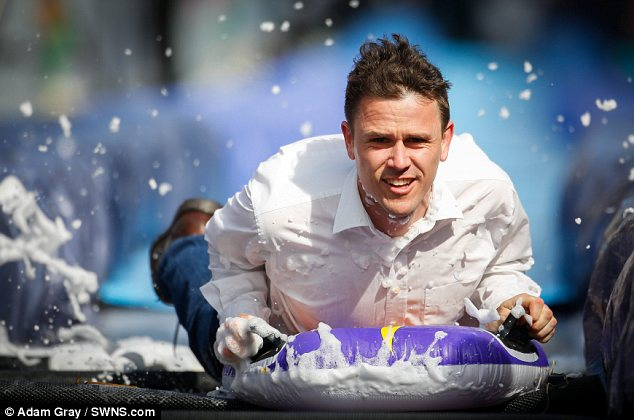 Go! Creator Luke Jerram slides down the giant 90m (300ft) water slide on Park Street, Bristol