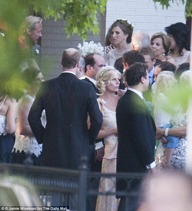 Hobnobbing: Prince William (center left) can be seen chatting to guests as the bride circulates