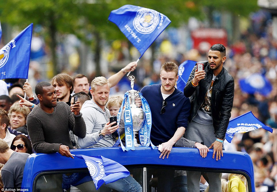Champions: City stars (from left) Wes Morgan, Kasper Schmeichel, Jamie Vardy and Riyad Mahrez work their smartphones on the bus