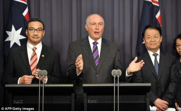 Australia's Transport Minister Warren Truss (centre) speaks during a press conference with Malaysia's Transport Minister Hishammuddin Hussein (left) and Chinese Transport Minister Yang Chuantang (second right) after talks about missing Malaysia Airlines flight MH370. Experts are to re-examine information gathered so far