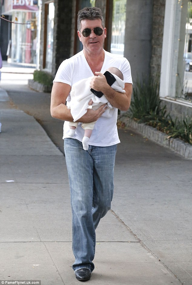 Proud dad: The star has been relishing in his new role as a father, spotted here a couple of weeks ago carrying Eric through Los Angeles
