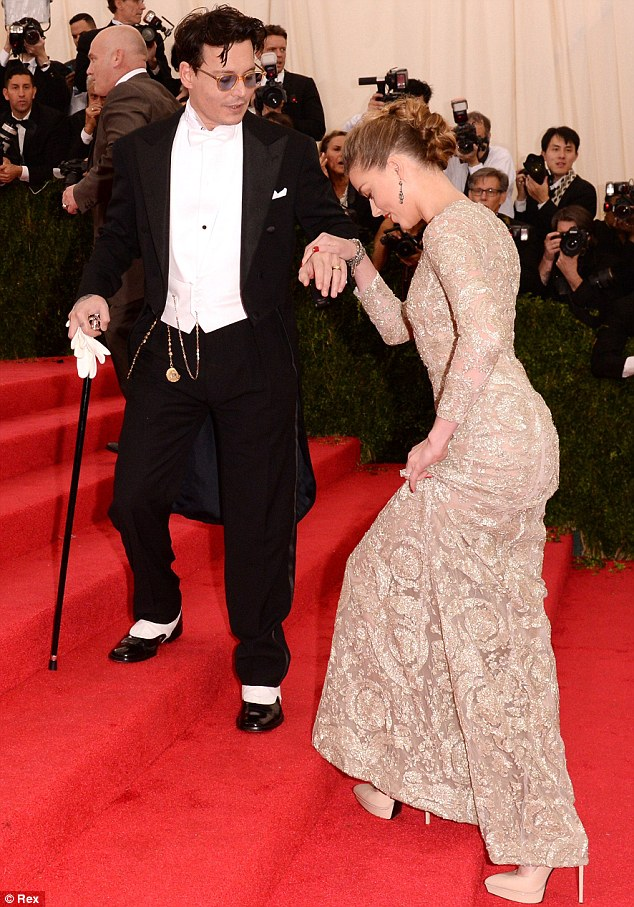 Helping hand: Johnny Depp and his fiancé Amber Heard channeled old Hollywood glamour at the Met Gala on Monday as he wore Ralph Lauren and she donned a Giambattista Valli Haute Couture gown