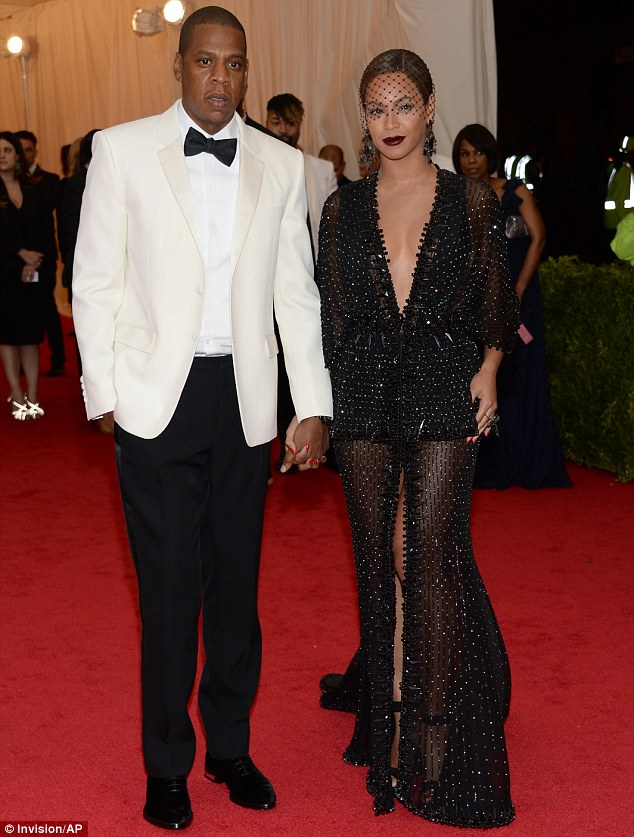 Taking the plunge! Beyoncé looked striking alongside Jay-Z in a plunging transparent black gown blanketed in beads and sequins, while harkening back to the 1920s with a net headpiece