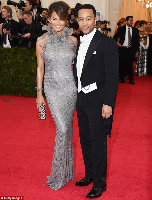Gorgeous in grey: Chrissy Teigen glowed alongside husband John Legend in a slinky silver gown featuring quirky ruffles around the collar and shoulders
