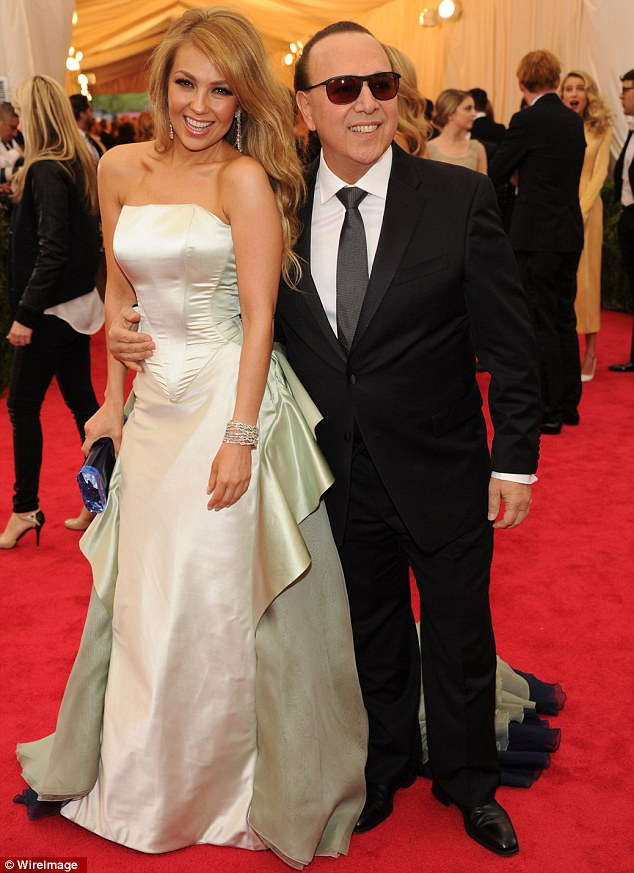 Glowing: Thalia looked splendid next to husband Tommy Mottola in a shining white gown that complimented her golden skin tone
