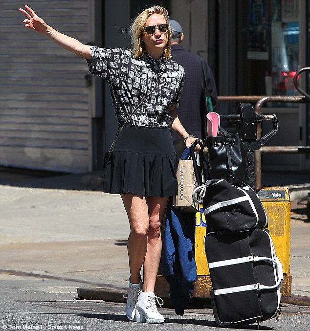 Hailing a cab: Chloe was seen with one hand outstretched while wearing a black and white patterned shirt and the actress also showcased her slim pins in a floaty black miniskirt
