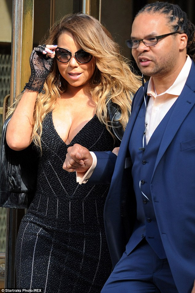 Sun-kissed: Mariah Carey showed off her signature glow as she shielded her eyes with cat-eye shades