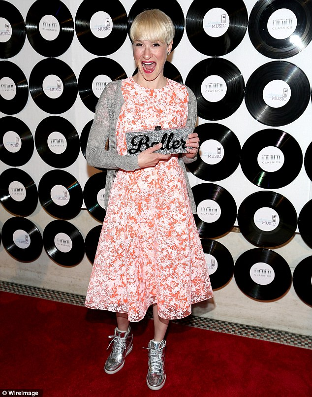 She's a baller! Socialite Julie Macklowe displayed her fun, child-like side in a white tea-length dress featuring pretty orange-red pattern, paired with a silver cardigan, matching shiny metallic high-top sneakers and a sparkly clutch