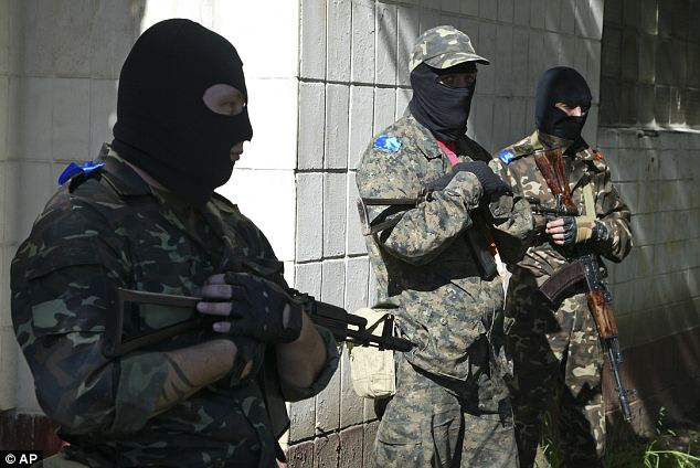 Civil war?: Pro-Russian gunmen hold their weapons yesterday as they try to block a military base of Ukrainian riot police in Donetsk.