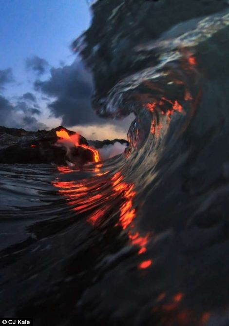 The intrepid duo had to enter the water within feet of where the lava was running into the surf, braving the scalding water and dodging ¿lava bombs¿ floating towards them