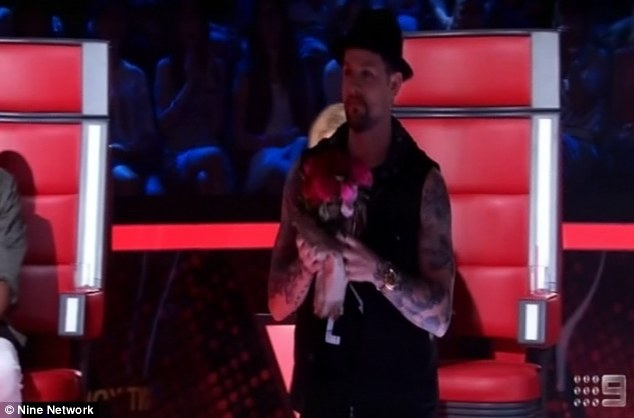 Touch of romance: The tattooed star had a trick up his sleeve and pulled a bouquet of roses from behind his chair and promptly presented them to the gorgeous 25-year-old