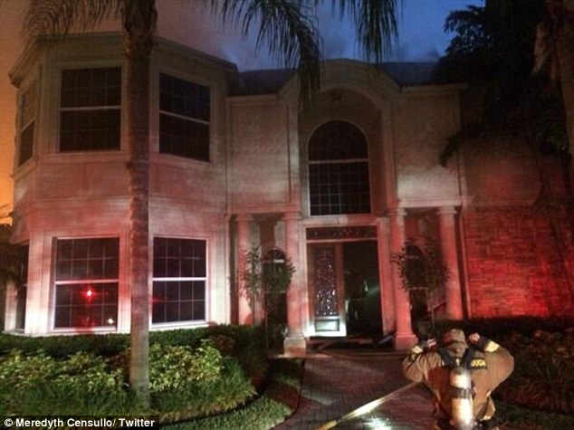 Scene: A firefighter is seen entering the smoke-filled mansion in the early hours of Wednesday morning