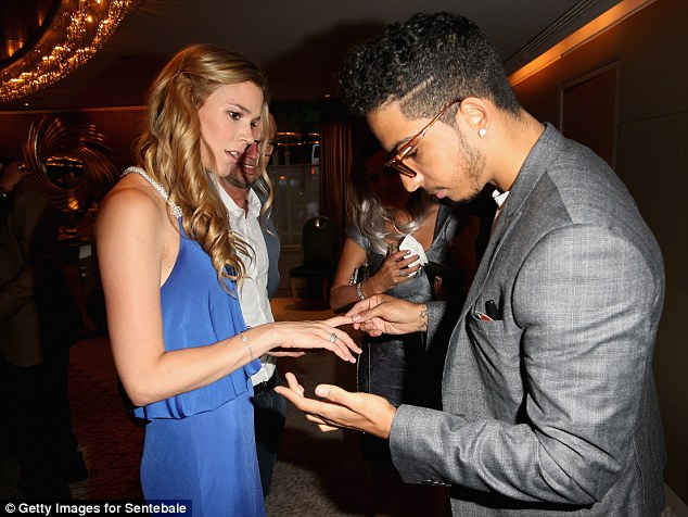 Singer Joss Stone is shown a magic trick by magician Troy as they attend the Sentebale Summer Party at the Dorchester Hotel