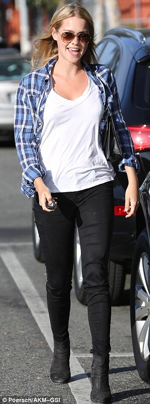 Off duty: The 25-year-old  wore a relaxed outfit of black jeans, white T-shirt and a blue checked shirt, which she accessorised with black heeled boots and aviator sunglasses