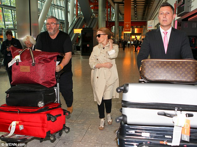 Not so light traveller: The singer needed two assistant to push her luggage when she arrived at Heathrow