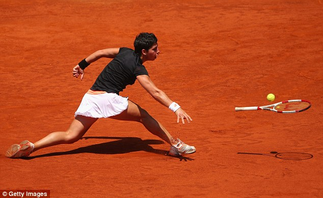 Last throw of the dice: Carla Suarez Navarro throws her racket at the ball as she suffers a straight-sets defeat
