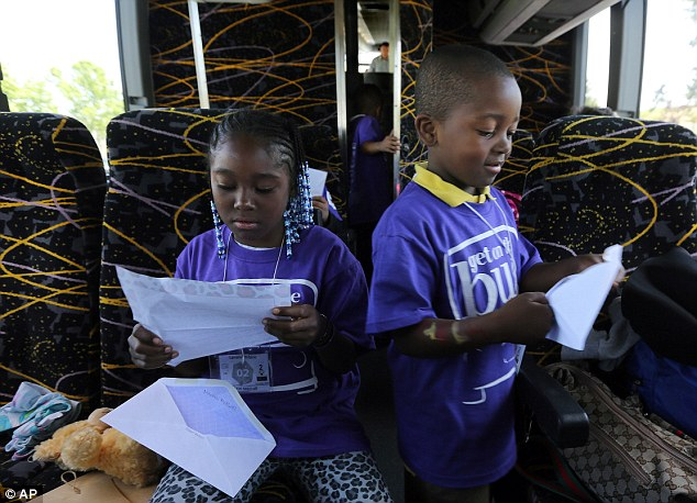 Lamariae Williams, 10, left, looks at a letter from her mother, Taryn Mitchell, an inmate at the Folsom Women's Facility, as her brother, Lamar Williams, 6, opens his, on the bus that will take them home after visiting their mother