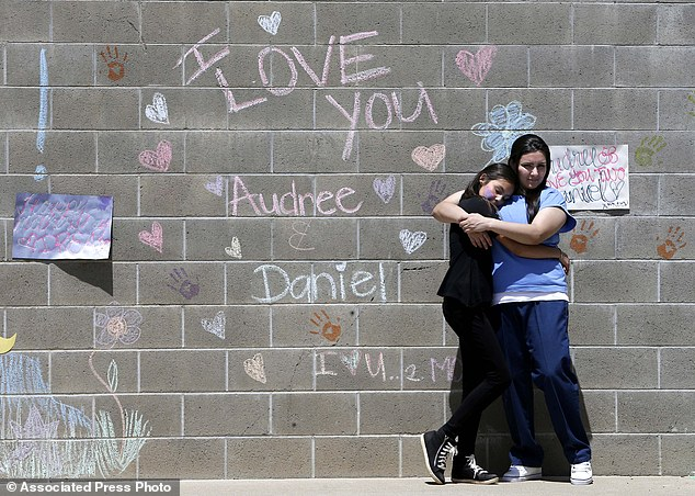 Audree Loaiza,11, left, hugs her mother, inmate Andrea Fabbri during her visit at the Folsom Women's Facility near a wall where Fabbri and her daughter drew loving messages to one another in chalk