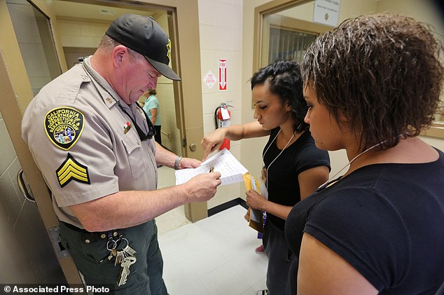 Correctional Sgt. Ron Crother checks in Samantha, center, and Summer La France before their visit with their mother, Catherine La France, at the Folsom Women's Facility where she is serving three more years for petty theft