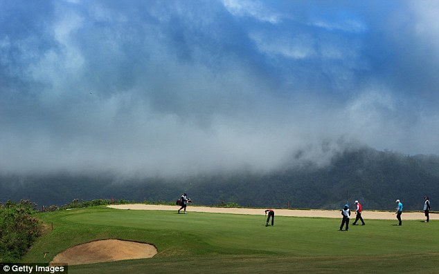 Stunning: Players prepare to putt on the picturesque 4th green at Club de Golf do Santo da Serra in Portugal