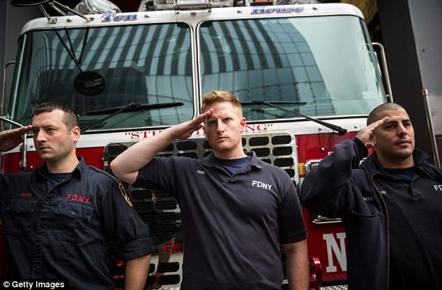 Paying respects: Firefighters stand to attention as the emergency vehicles transport the remains to Ground Zero