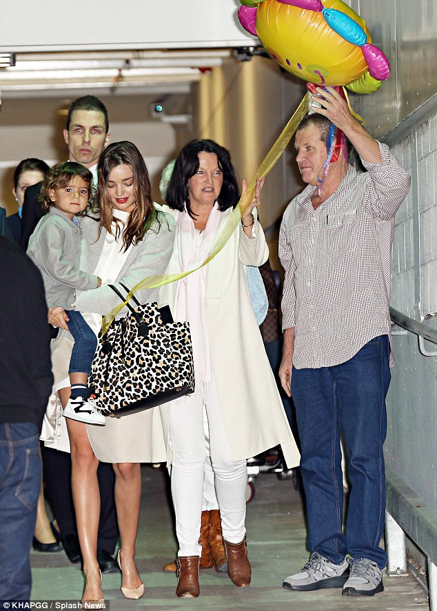 Quite a welcome home party: Miranda Kerr, 31, was met by her three-year-old son Flynn and her parents Therese and John as she arrived at Sydney Airport on Saturday night