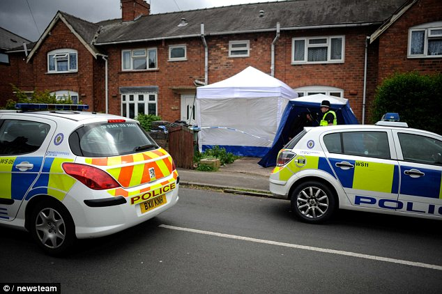 Patrol: Police stand outside the property on Hollemeadow Avenue in Walsall