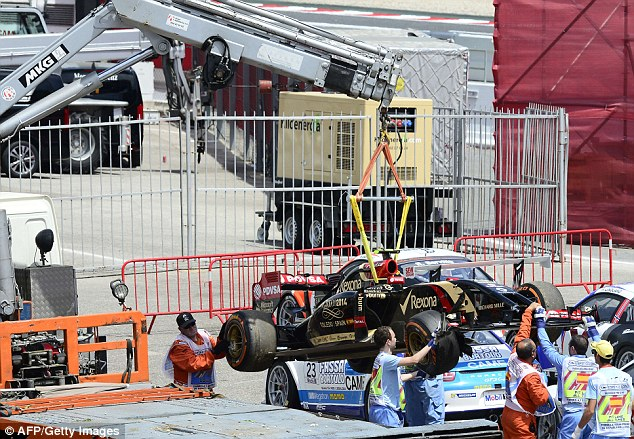 End of the road: Pastor Maldonado's Lotus is loaded on to a tow truck after his crash during qualifying