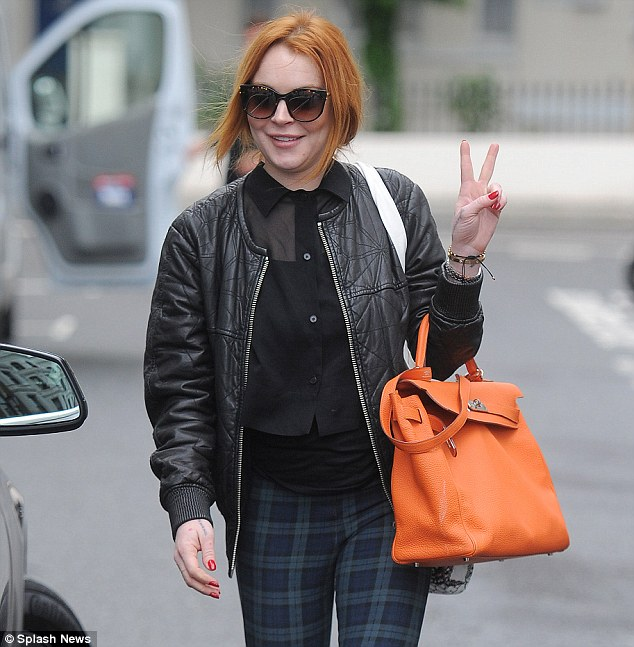 Peace out: Lindsay looked extremely happy as she left the salon while flashing the peace sign