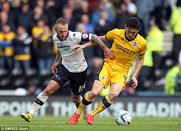 Tussle: Brighton's Keith Andrew (right) has Derby's Johnny Russell in hot pursuit