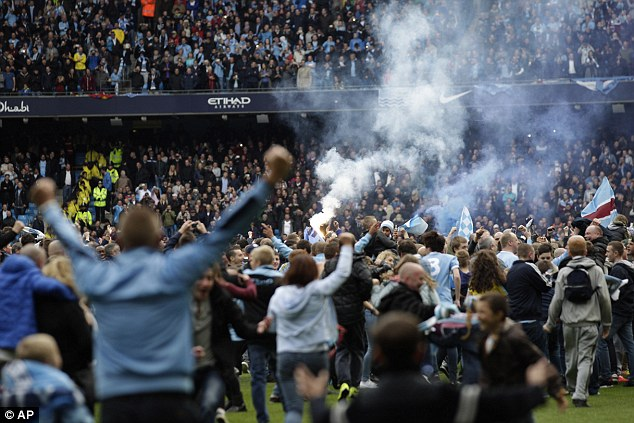 Smokin': Fans storm the pitch to mob their heroes after the title is secured on the final afternoon