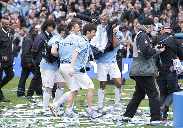 Cheer: Even Manuel Pellegrini managed a smile as he was carried around by his players