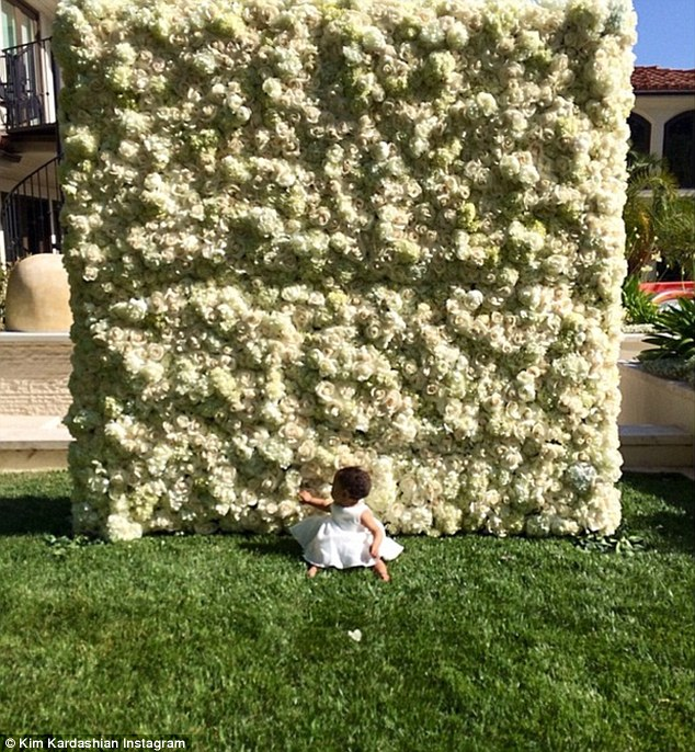 Little princess! North is seen sitting in front of the wall of flowers wearing an adorable white dress