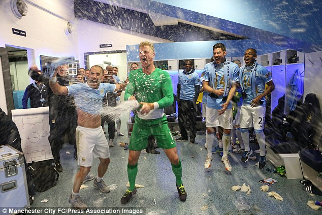 Champagne moment: Joe Hart sprays the bubbly as Man City celebrate their second title in three years
