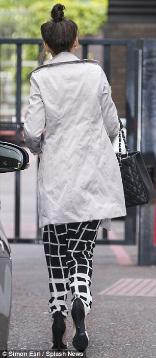 Exit: The raven-haired beauty matched her fetching pair of trousers with a pair of black and white heeled shoes and she put on a coat and tied her hair up just before departing the studios