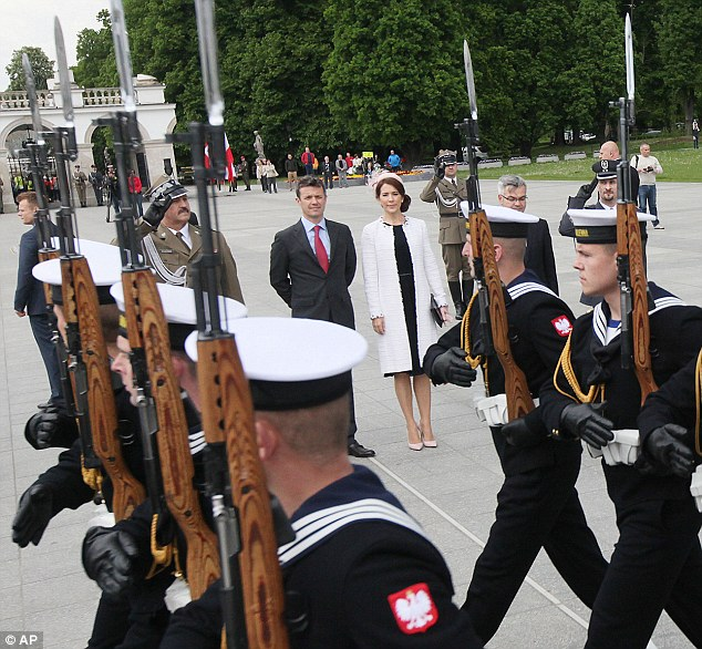 Crown Prince Frederik and Crown Princess Mary watch a military parade following a wreath laying ceremony