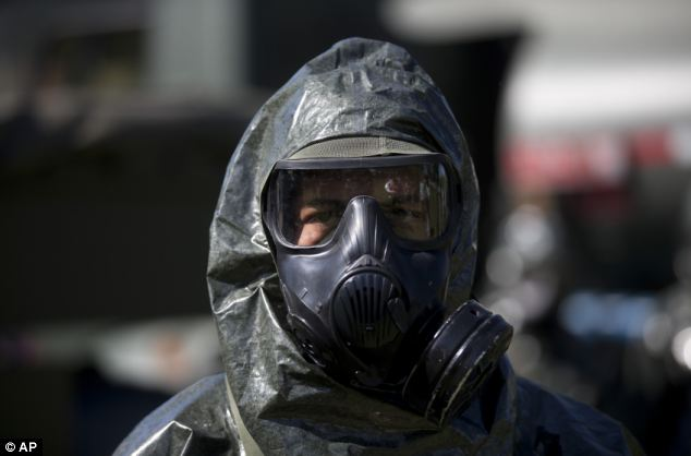 Preparations: A soldier wears a chemical suit during the presentation of troops
