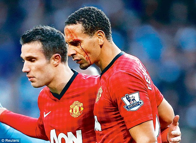 Hard man: Ferdinand is escorted from the pitch by Robin van Persie after being cut by a coin thrown from the crowd during a Manchester derby in 2012