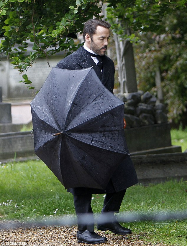 Funeral in the rain: Jeremy Pivens wears period costume for the drama set almost a century ago