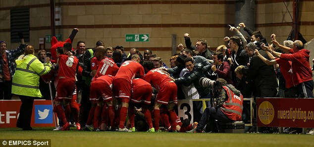 Elated: O's players pile on top of Cox after his opening goal of the play-off semi-final at the Matchroom Stadium