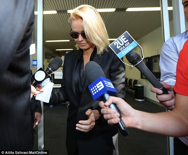 No comment: Hiding behind a thick-rimmed pair of aviators she kept her eyes downcast as she pushed past the waiting media
