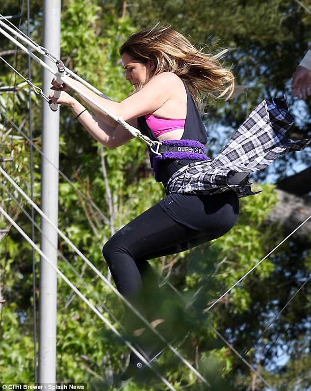 Soaring! Khloe gripped the ropes tautly while launching off of the platform