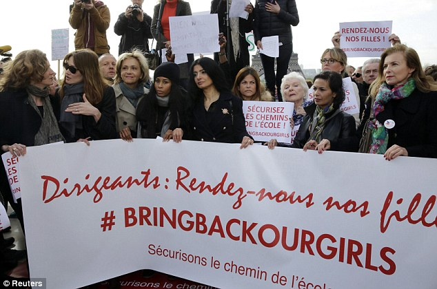 Former French first ladies Carla Bruni-Sarkozy (2nd left) and Valerie Trierweiler (right) stand with politicians and entertainment artists behind a banner which reads 'Leaders, bring back our girls', during a demonstration near the Eiffel Tower in Paris