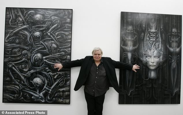 Swiss artist H.R. Giger poses with two of his works at the art museum in Chur, Switzerland