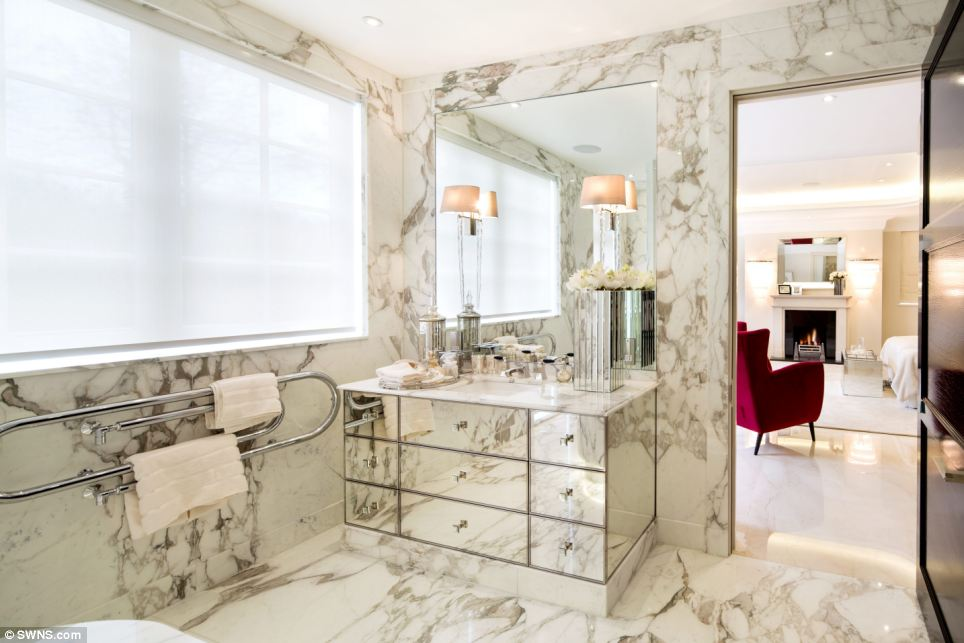 En suite: The master bedroom leads on to this opulent cream marble bathroom suite, which rivals those found in many top hotels
