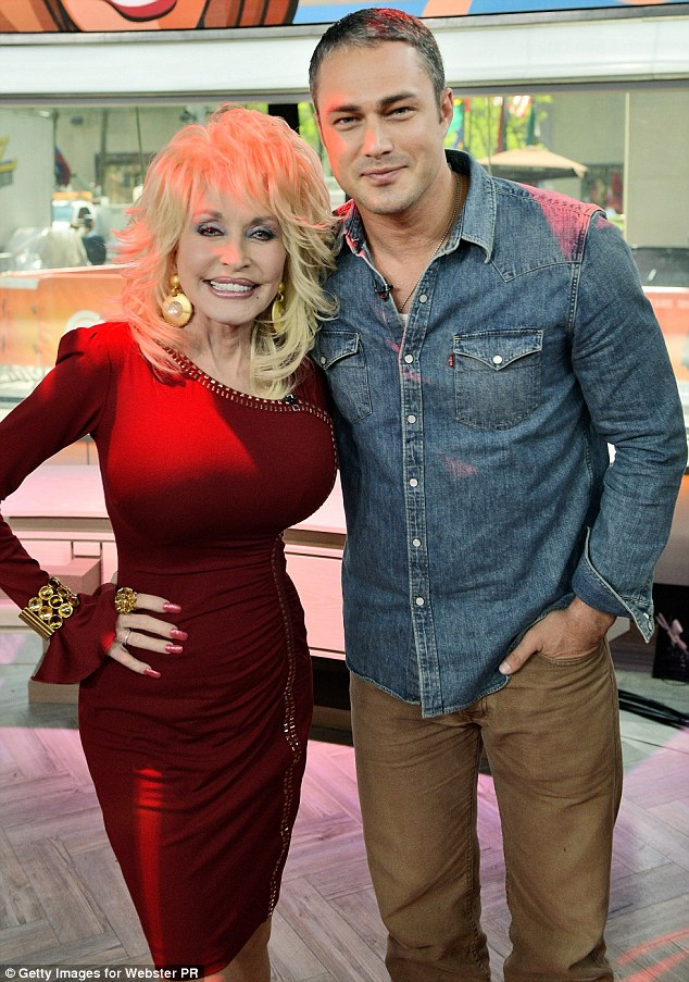 Everyone loves Dolly: Taylor Kinney posed with the legend, and perhaps asked for some fashion tips for girlfriend, Lady Gaga